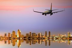 Passenger jet airliner plane arriving or departing San Diego. San Diego skyline with a commercial passenger jet airliner plane arriving or departing, night royalty free stock images