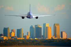 Passenger jet airliner plane arriving or departing Tampa International Airport in Florida at sunset or sunrise. Tampa, Florida, skyline with warm sunset light Royalty Free Stock Image