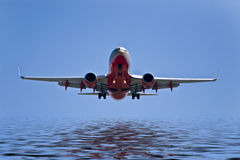 Passenger jet airplane flying over wat Royalty Free Stock Image
