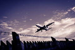 Passenger jet and airport perimeter fence Royalty Free Stock Photos