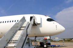 Passenger jet with attached ladder for service and refueling Stock Photos