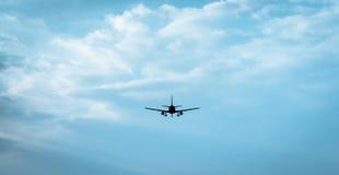 Passenger jet flying into cloudly horizon stock photos