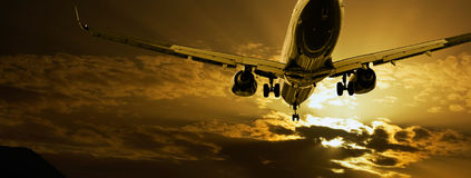 Passenger jet landing against amber sky Royalty Free Stock Photo