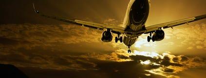 Passenger jet landing against amber sky. Passenger jet landing against amber sunset sky Royalty Free Stock Photo