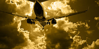 Passenger jet landing against amber sky Royalty Free Stock Images