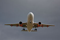 Passenger jet landing against a grey sky Stock Photography