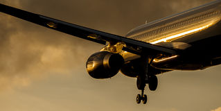 Passenger Aircraft Landing Approach at Sunset Stock Image