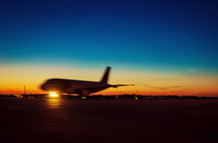 Passenger jet plane against beautiful dusky sky. Passenger jet plane preparing to take off from airport runways with motion blur against beautiful dusky sky Royalty Free Stock Photos