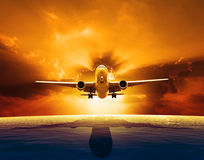 Passenger jet plane flying over beautiful sea level with sun set Stock Photo