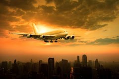 Passenger jet plane flying over urban scene against beautiful su Stock Images