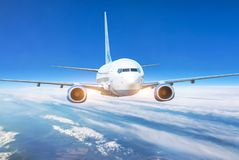 Free Passenger Jet Plane In The Blue Sky. Aircraft Flying High Through The Cumulus Clouds. Close Up View Airplane In Flight Stock Photo - 136900070