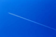 Passenger jet plane with a long trail on a blue sky Royalty Free Stock Photo
