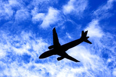 Passenger Jet Plane Silhouette on Cloudy Blue Sky royalty free stock image