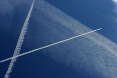 Passenger Jet Trails Crossing in a Blue Royalty Free Stock Images