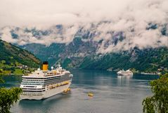 Passenger liner docked in port. Cruise ship in norwegian fjord. Travel destination, tourism. Adventure, discovery. Geiranger, Norway - January 25, 2010 stock photos