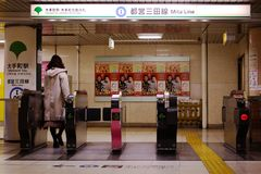 A Passenger passes through the ticket gates at Otemachi Station. Royalty Free Stock Images