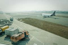A passenger plane being serviced by ground services before next takeoff. Pushback tug, passenger boarding steps vehicle, tractor with baggage carts and minivan stock photography