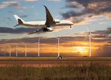 Passenger plane climbs above the farm field. Passenger plane takes off and climbs above the farm field and wind electric generators. Aircraft fly in the bright Stock Images