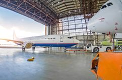 Passenger plane with a damaged engine is push roll up tow tractor to the hangar for repair, maintenance. Passenger plane with a damaged engine is push roll up royalty free stock images