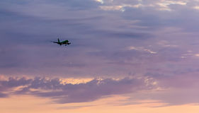 Passenger plane flies high in the sky in the rays of the sunset goes Royalty Free Stock Photography