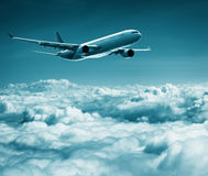 Passenger plane flies over cumulus clouds Royalty Free Stock Photos