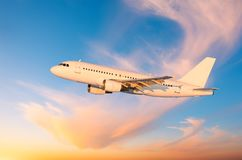 Passenger plane flies in the sky against the background of cirrus clouds during sunset, the shadow from the wing on the fuselage. Stock Photos