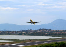 Passenger plane fly down over take-off runway from airport Royalty Free Stock Photography