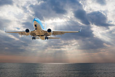 Passenger plane fly down over take-off runway from airport Stock Photos