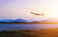 Passenger plane fly up. Over take-off runway from airport at sunset Stock Image