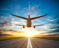 Passenger plane fly up over take-off runway. At sunset. Dramatic sky on background. Travel concept Stock Images