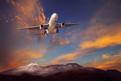 Passenger plane flying above rock mountain against beautiful dus Royalty Free Stock Photos