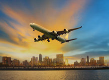 Passenger plane flying above urban scene use for convenience air Stock Image