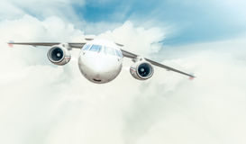 Passenger plane flying in blue cloudy sky. Stock Image