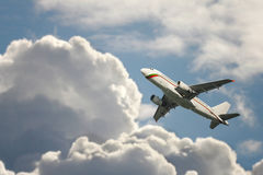 A passenger plane flying in the cloudy sky Royalty Free Stock Photography