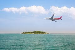 Passenger plane flying over beautiful blue ocean and island sea beach use for summer holiday vacation traveling stock images