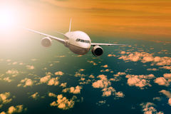 Passenger  plane flying over beautiful light sky for air traveli Stock Photos