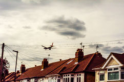 Passenger plane flying over the roofs of residential homes, low Royalty Free Stock Image