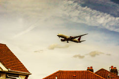 Passenger plane flying over the roofs of residential homes, low Stock Images