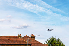 Passenger plane flying over the roofs of residential homes, low stock image