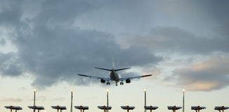 Passenger plane landing. Plane flying over the end of runway lights just before touching down Stock Photos