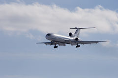 Tu-154M. Passenger plane sits isolated on a blue sky background Stock Photos