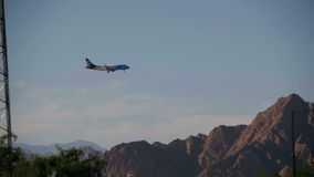 Passenger Plane in the Sky Landing on the Background of Mountains and Palm Trees in Egypt. Slow Motion. EGYPT, SOUTH SINAI, SHARM EL SHEIKH, DECEMBER 3, 2016 stock video footage