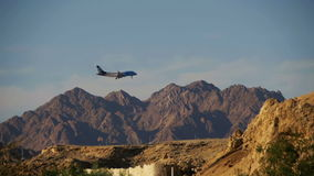 Passenger Plane in the Sky Landing on the Background of Mountains and Palm Trees in Egypt. Slow Motion. EGYPT, SOUTH SINAI, SHARM EL SHEIKH, DECEMBER 3, 2016 stock footage