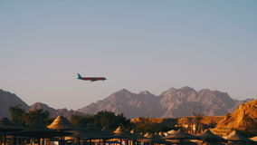 Passenger Plane in the Sky Landing on the Background of Mountains and Palm Trees in Egypt. EGYPT, SOUTH SINAI, SHARM EL SHEIKH, DECEMBER 3, 2016: Passenger stock video