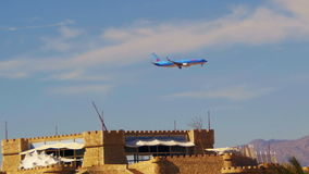 Passenger Plane in the Sky Landing on the Background of Mountains and Palm Trees in Egypt. EGYPT, SOUTH SINAI, SHARM EL SHEIKH, DECEMBER 3, 2016: Passenger stock video footage
