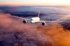 Passenger plane in the sunset sky. Sunset flight. The passenger wide body aircraft flies high above the colored clouds Stock Image