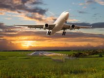 Passenger plane takes off from the airport runway. Aircraft fly during the sunset. Airplane front view Royalty Free Stock Photography