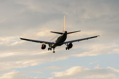 Passenger plane was landing. Departing passenger aircraft in the sky with clouds Stock Images