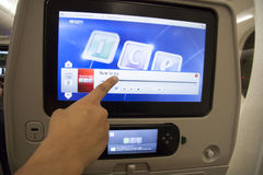 Passenger pointing at the touch screen in a plane Royalty Free Stock Image