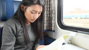 Passenger read book while traveling by train. Young beautiful woman read her book beside window while traveling by train stock video